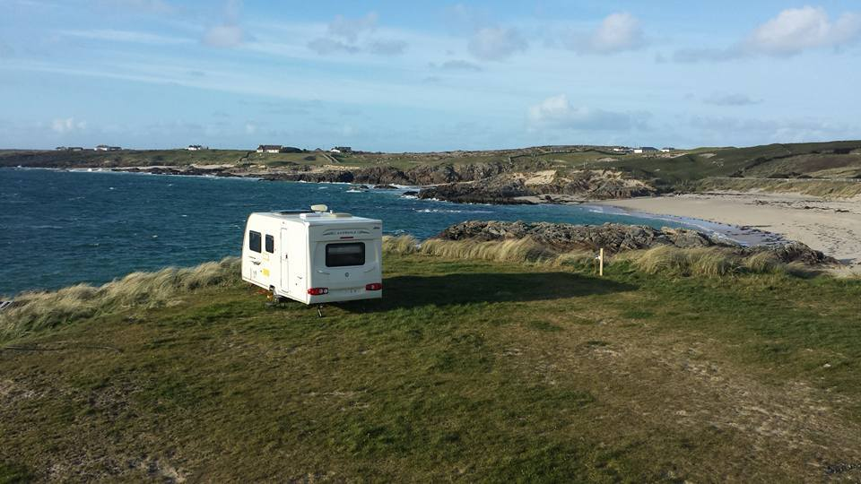 Spacious caravan pitch looking out to see near a white sand bay