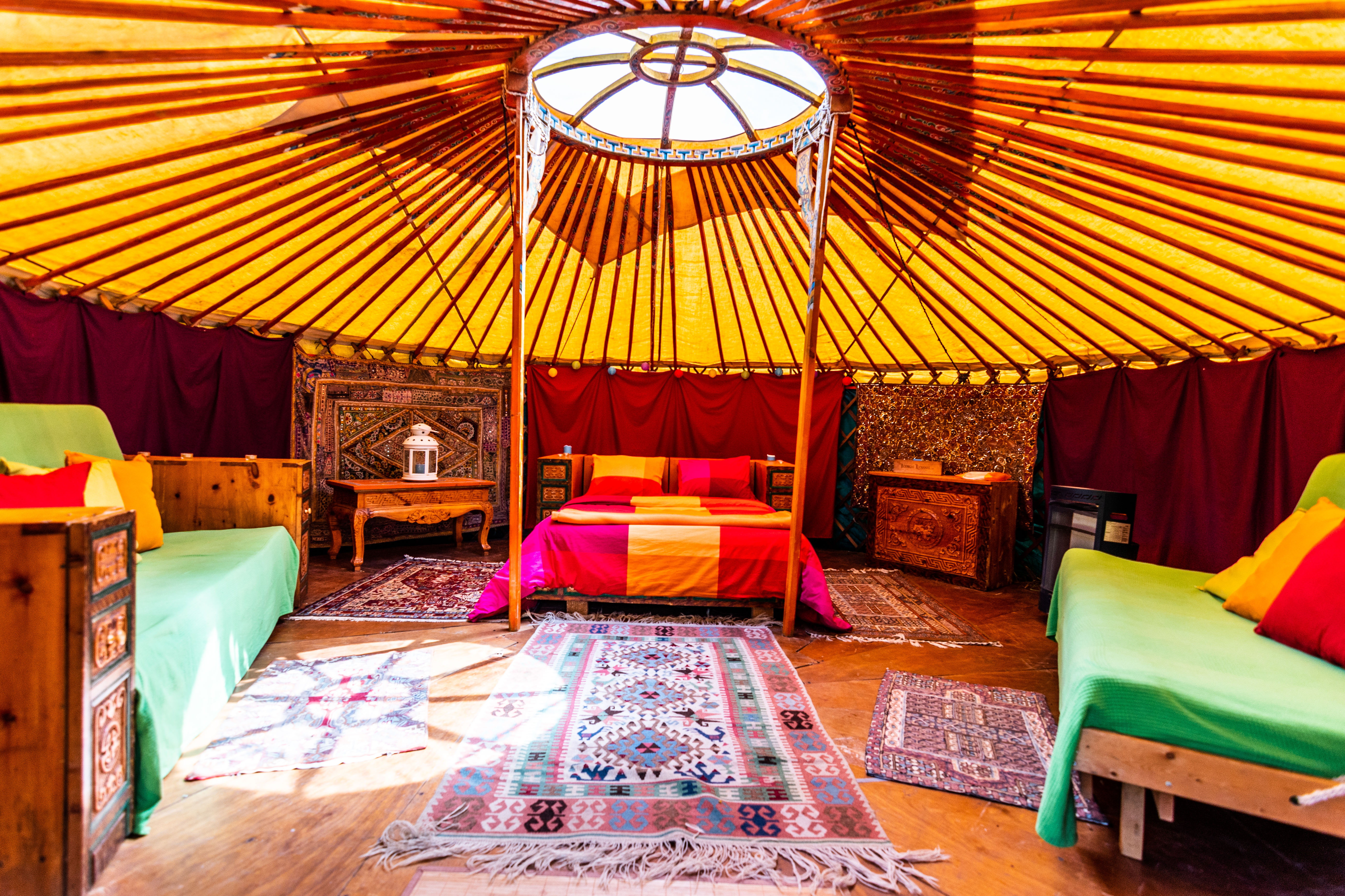 Inside yurt with double bed, rugs and futons