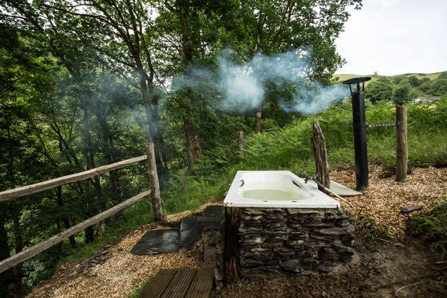 Woodfired open air bath tub surrounded by woodland