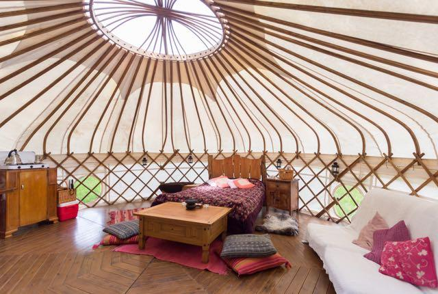 Inside yurt, double bed, futon and wooden furniture