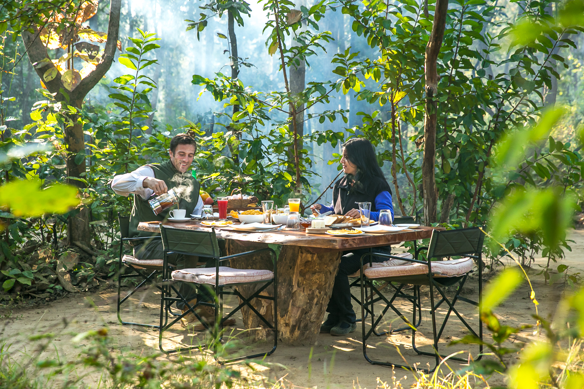 Couple having breakfast surrounded by morning mist through jungle