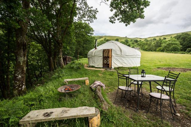 Yurt in field with outside dining table and fit pit